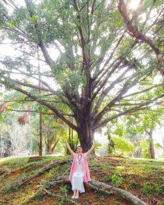 Monja Bianca Toffani sentada em uma árvore